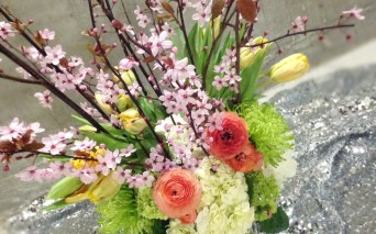 Beautiful floral arrangement made with tulips, cherry blossoms, hydrangeas and ranunculus.